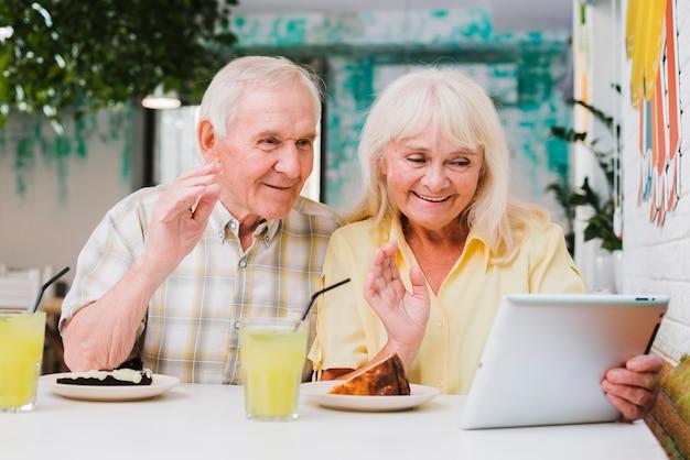 Couple de personnes âgées ayant un appel vidéo sur tablette Photo gratuit