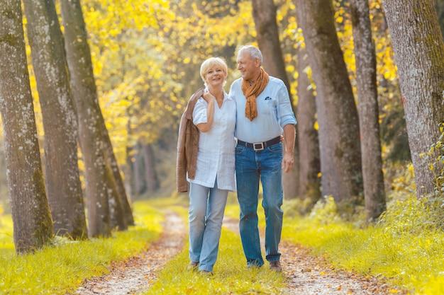 Couple de personnes âgées ayant des loisirs à pied dans les bois Photo Premium
