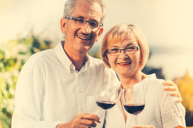Couple de personnes âgées bénéficiant d'un vin rouge à l'extérieur Photo Premium