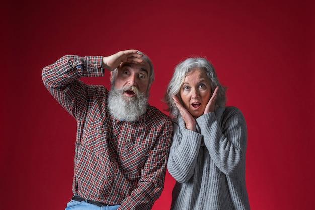 Couple De Personnes âgées Choqué à La Recherche D'appareil Photo Sur Fond Rouge Photo gratuit