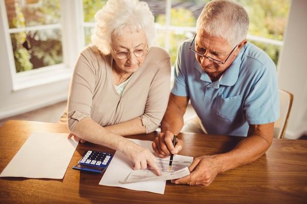 Couple de personnes âgées comptant des factures à la maison Photo Premium