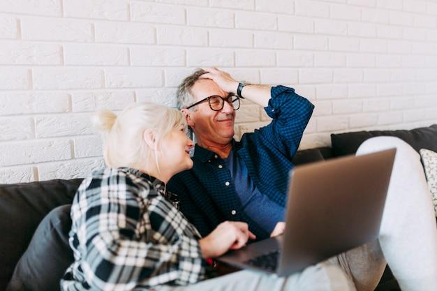 Couple de personnes âgées dans la maison de retraite avec ordinateur portable Photo gratuit
