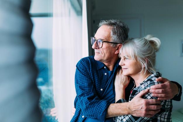 Couple De Personnes âgées Dans La Maison De Retraite Regardant Par La Fenêtre Photo gratuit