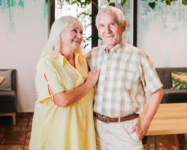 Couple de personnes âgées embrassant debout à la maison Photo gratuit