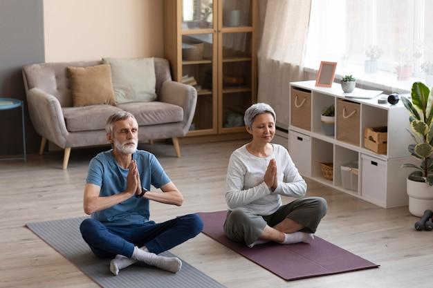 Couple De Personnes âgées Exerçant Ensemble à La Maison Photo gratuit