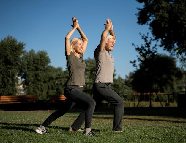 Couple De Personnes âgées Faisant Du Yoga En Plein Air Photo Premium