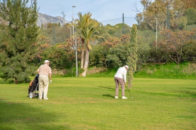 Couple De Personnes âgées Jouant Au Golf Sur Le Green Photo Premium