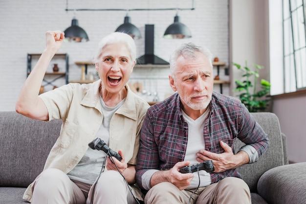 Couple de personnes âgées jouant à des jeux vidéo Photo gratuit