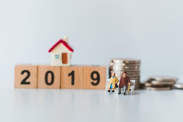 Couple de personnes âgées miniatures assis sur une année en bois 2019 et empiler des pièces Photo Premium