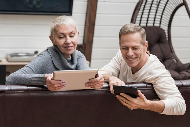 Couple De Personnes âgées Passer Du Temps Ensemble Sur Leurs Appareils Photo gratuit