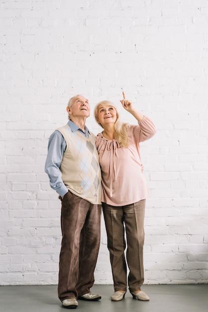 Couple De Personnes âgées Pointant Vers Le Haut Photo gratuit