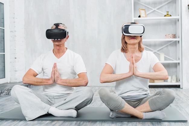 Couple de personnes âgées portant le casque de réalité virtuelle assis sur un tapis avec le geste des mains en prière Photo gratuit