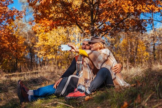 Couple De Personnes âgées Prenant Selfie En Automne Parc. Heureux Homme Et Femme Profitant De La Nature Et Des Câlins Photo Premium