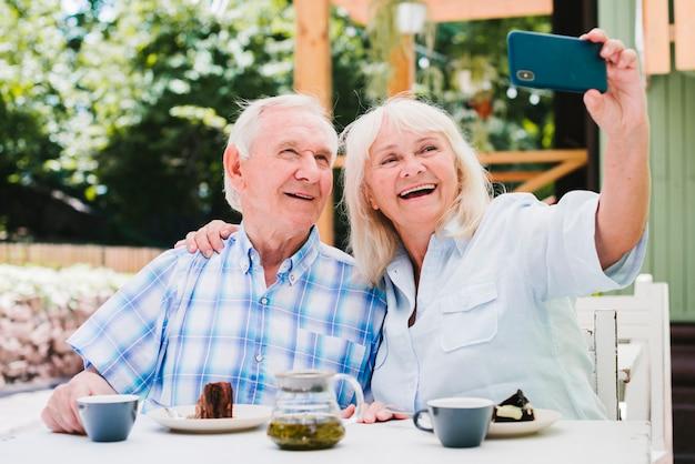 Couple de personnes âgées prenant selfie souriant assis sur la terrasse extérieure Photo gratuit