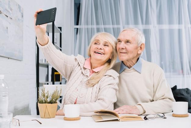 Couple de personnes âgées prenant selfie Photo gratuit