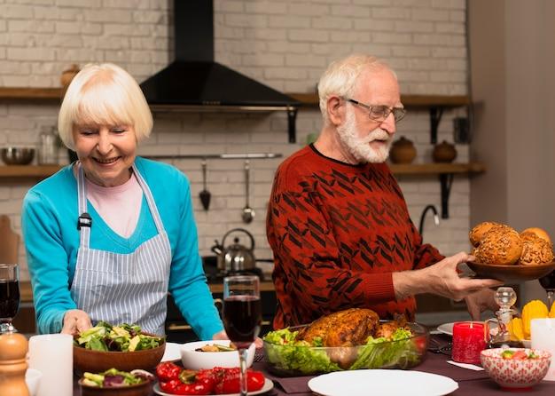 Couple de personnes âgées préparant le repas de thanksgiving Photo gratuit