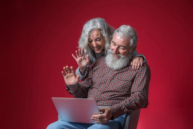 Couple De Personnes âgées Regardant Un Ordinateur Portable Et Agitant Leurs Mains Sur Un Fond Rouge Photo gratuit