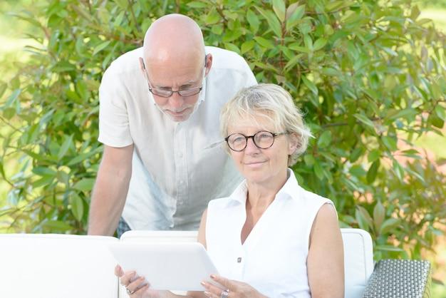 Un Couple De Personnes âgées Regarde Une Tablette Numérique Photo Premium