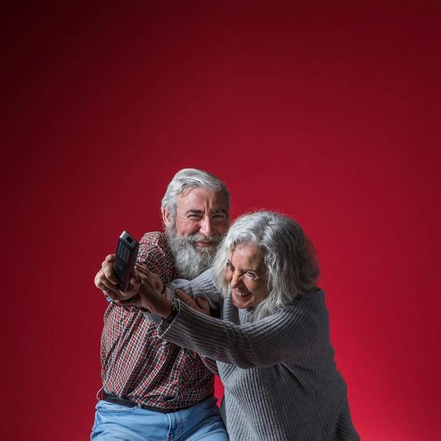Couple de personnes âgées se battant pour la télécommande sur fond rouge Photo gratuit