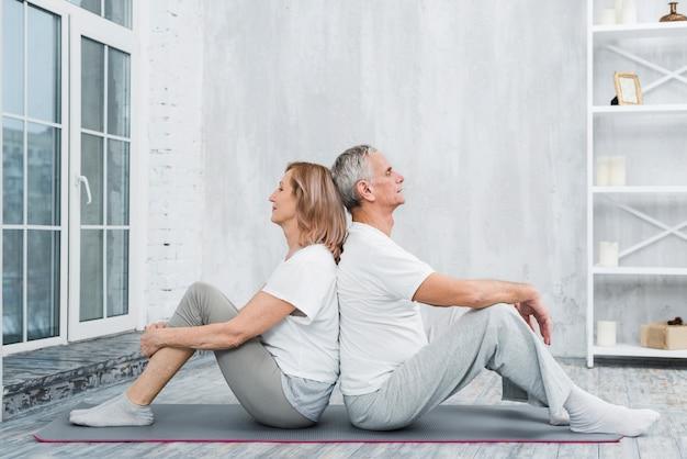 Couple de personnes âgées se reposer après l'exercice dans le salon Photo gratuit
