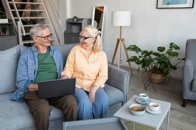 Couple De Personnes âgées Smiley Coup Moyen Avec Ordinateur Portable Photo gratuit