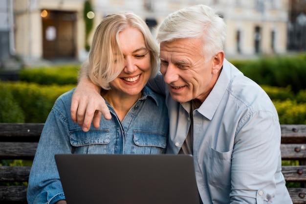 Couple De Personnes âgées Smiley Embrassé à L'extérieur Avec Ordinateur Portable Photo Premium