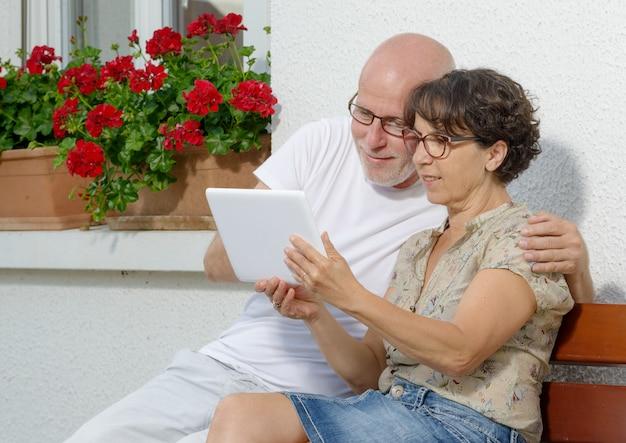 Couple de personnes âgées avec une tablette, en plein air Photo Premium