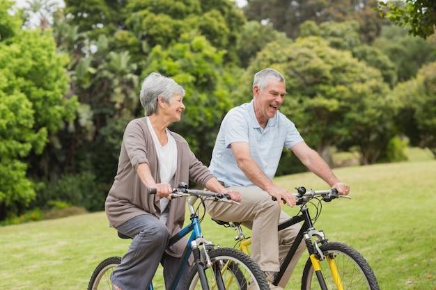 Couple de personnes âgées à vélo dans la campagne Photo Premium