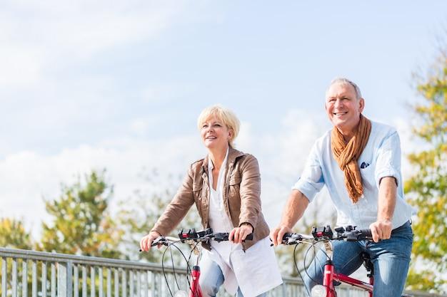 Couple de personnes âgées avec des vélos sur le pont Photo Premium