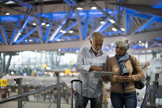 Couple de personnes âgées voyageant à l'aéroport Photo Premium
