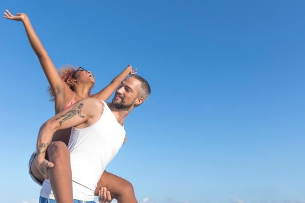 Couple piggy back sur la plage en été Photo Premium