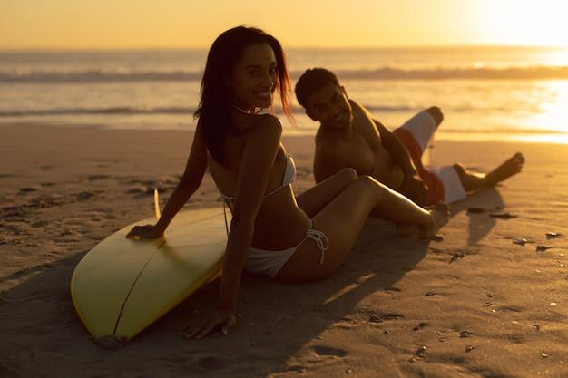 Couple avec planche de surf relaxant sur la plage au crépuscule Photo gratuit