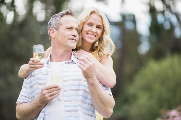 Couple portant un toast avec du champagne à l'extérieur Photo Premium