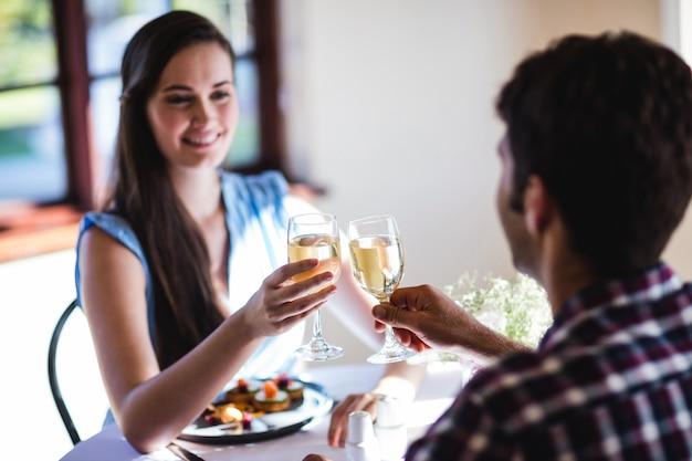 Couple portant un verre de vin blanc au restaurant Photo Premium