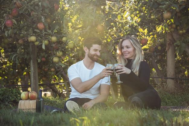 Couple portant un verre de vin dans un verger de pommiers Photo gratuit