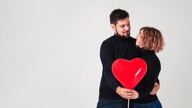 Couple Posant Avec Ballon Pour Saint Valentin Et Espace De Copie Photo gratuit