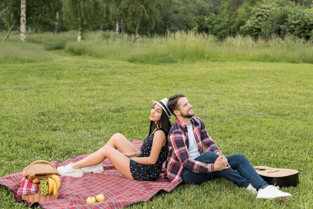Couple posant sur une couverture de pique-nique Photo gratuit