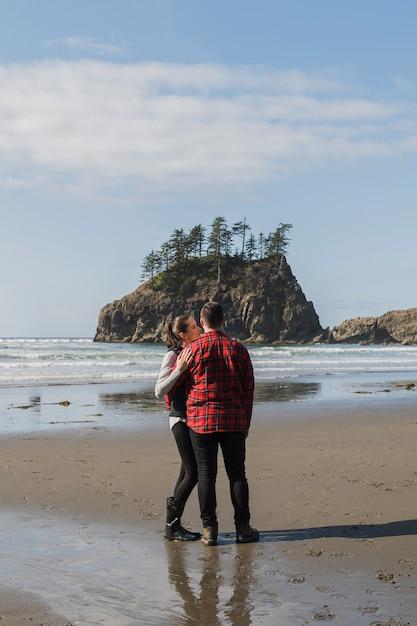 Couple posant embrassé sur le rivage Photo gratuit