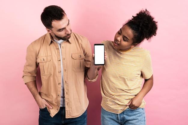 Couple Posant Intrigué Par Smartphone Photo gratuit
