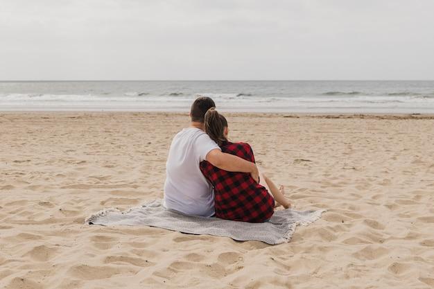 Couple posant sur la plage embrassé Photo gratuit