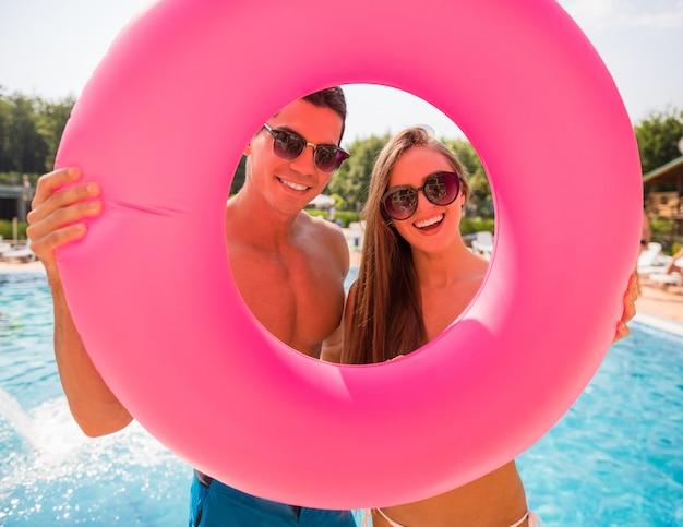 Couple pose avec anneau en caoutchouc dans la piscine. Photo Premium