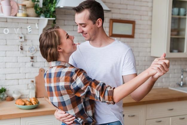 Couple positif embrassant et dansant dans la cuisine Photo gratuit
