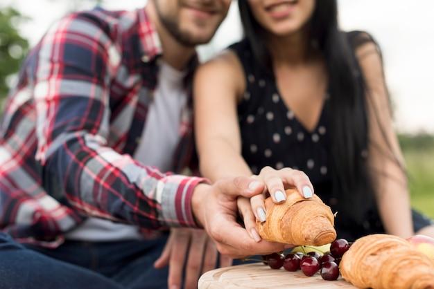 Couple prenant un croissant dans le parc Photo gratuit