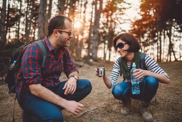 Couple prenant un frein après une randonnée pour boire une eau Photo Premium