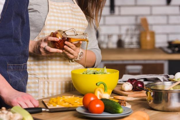 Couple préparant une salade de légumes dans la cuisine Photo gratuit