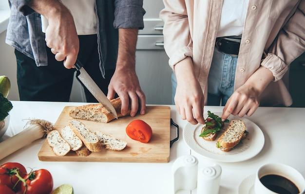 Couple Préparer Des Sandwichs Ensemble Tout En Tranchant Du Pain Et Des Légumes Dans La Cuisine Photo Premium