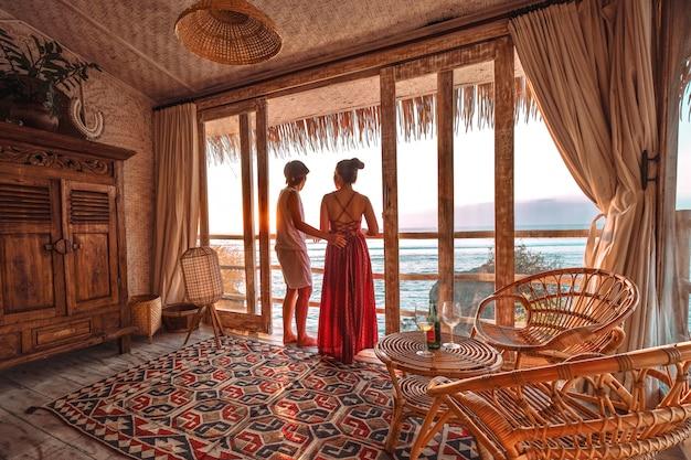 Couple profitant des vacances du matin sur un bungalow de plage tropicale à la recherche d'une vue sur l'océan vacances reposantes à uluwatu bali, indonésie Photo Premium