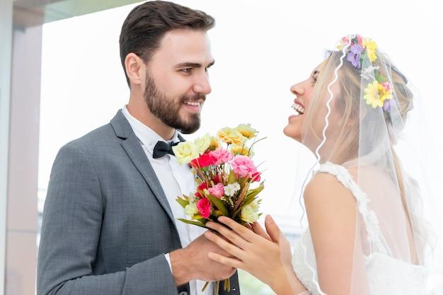 Couple De Race Blanche, Le Marié Donne La Mariée Actuelle Dans Le Studio De Mariage. Photo Premium