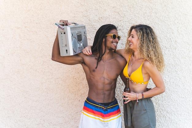 Couple de race mixte tenant une vieille cassette radio. Photo Premium