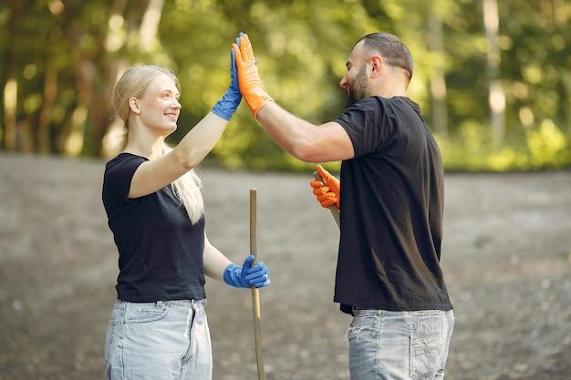 Couple Ramasse Des Feuilles Et Nettoie Le Parc Photo gratuit